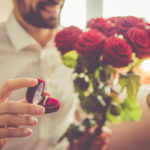 Man holding engagement ring and roses